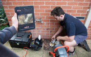 plumber using a drain camera to do an inspection of blocked drain